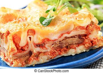 Lasagna - Portion of lasagna garnished with salad greens