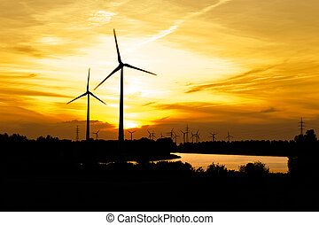 Wind turbine farm over sunset - Silhouette of wind turbine...