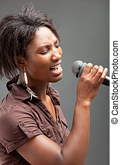 Black Woman Singing Into Microphone , on grey background