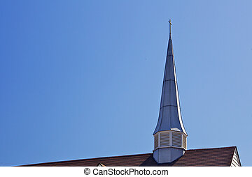Thin Church spire and partial roof against a blue sky