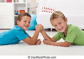 Happy boys laughing and arm wrestling - Happy kids laughing...