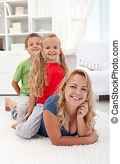 Family quality time - woman with kids laying on the floor at...