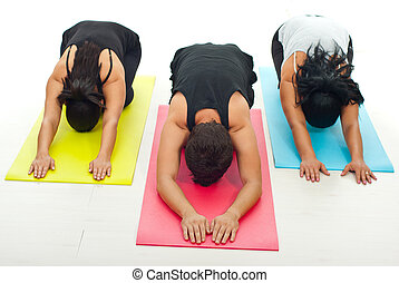 Group of people doing yoga exercise - Group of three people...