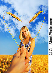 Beautiful girl standing in the wheat field and heart shaped...