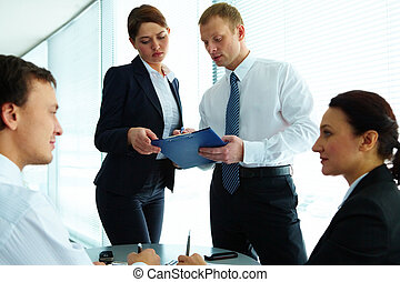 Office work - Image of confident colleagues communicating in...