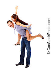 Happy young female enjoying a piggyback ride on boyfriends...