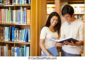 Students looking at a book in the library