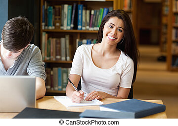 Smiling student writing a paper in the library