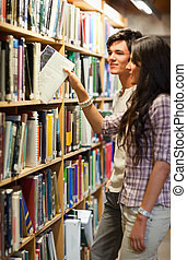 Portrait of  young students choosing a book