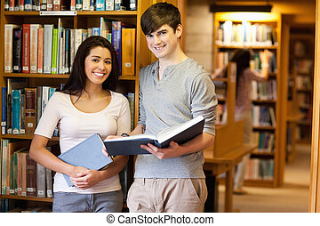 Beautiful students with a book in a library