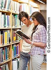 Portrait of young students looking at a book in a library