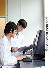 Male scientists using a monitor in a laboratory