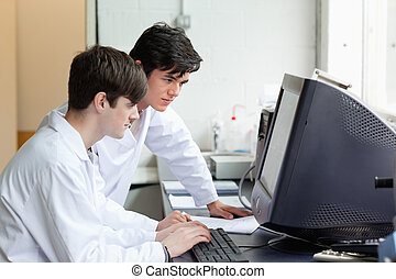 Scientists working with a monitor in a laboratory