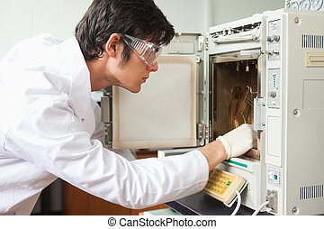 Male scientist using a laboratory chamber furnace wearing...