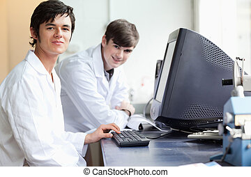 Students posing with a monitor in a laboratory