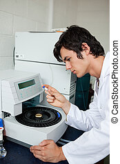Portrait of a a student using a centrifuge in a laboratory