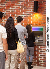 Portrait of people queuing to withdraw cash at an ATM