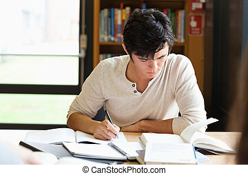 Male student working on an essay in a library