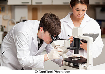 Scientist looking in a microscope while his colleague is taking notes in a laboratory