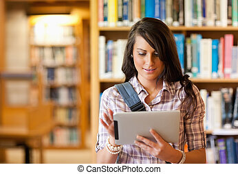 Cute young student using a tablet computer in a library