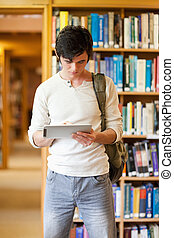 Portrait of a focused student using a tablet computer in a...