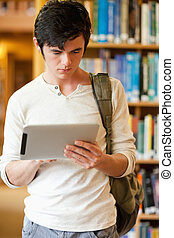 Portrait of a serious student using a tablet computer