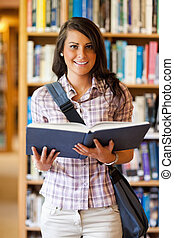 Portrait of a cute young student holding a book