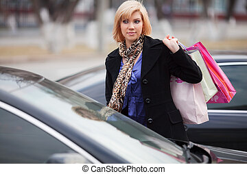 Young shopper on a car parking - Young woman with shopping...