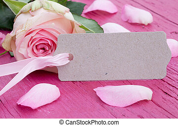 Pink rose with gift tag on rustic wood