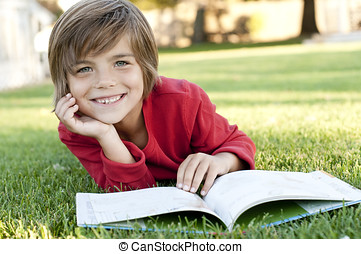 boy reading - Very cute 7 year old boy lying on the grass...