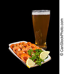 fried shrimps and beer on black background