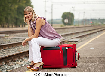 woman with luggage waiting train on railroad