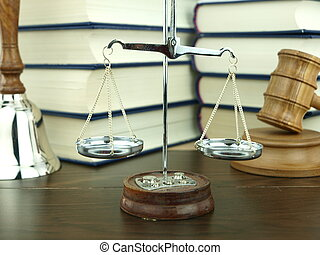 Scale of justice, hand bell and judges gavel with a stack of...