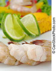 Closeup of raw king prawns with lime slices and lettuce on...