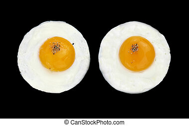Fried eggs like eyes - Two fried eggs like eyes in a black...