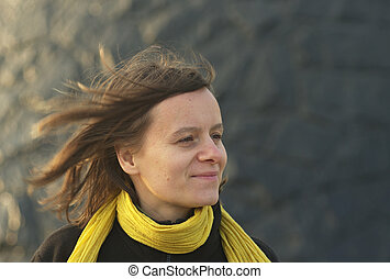 Young caucasian woman with yellow scarf and hair blowing in...