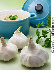 Garlic with creamy soup in blue pot