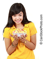 smiling teenage girl holding a bowl of cut fruits