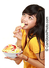 young girl holding a bowl of sliced fruits