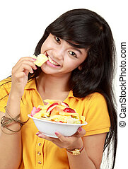smiling teenager eating a bowl of cut fruits