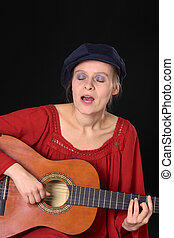 Young Caucasian woman singing and playing the guitar (Selective Focus, Focus on the face, hands and the guitar)