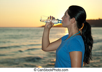 Profile of woman drinking water on the beach