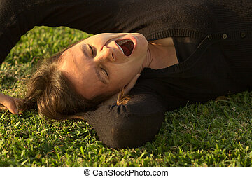 Young Caucasian woman yawning while lying on grass in a park lit by the evening light (Selective Focus, Focus on the eyes)