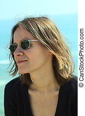 Portrait of a young woman in sunglasses on the coast (Selective Focus, Focus on the left side of the face)
