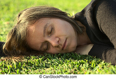 Young Caucasian woman sleeping on grass in a park lit by the evening light (Selective Focus, Focus on the left eye)