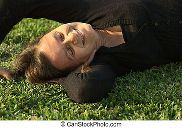 Young Caucasian woman enjoying the evening light in a park lying on the grass (Selective Focus, Focus on the face)
