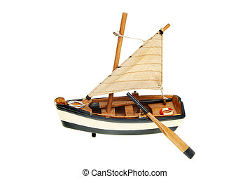 Model boat - Model sailing dinghy with oar isolated against...