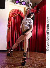 Stripper dancing on pole - Strip tease dancer posing at the...