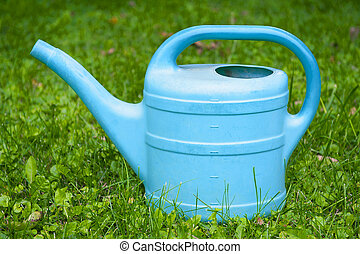 Watering can in the green grass