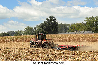 Tractor Plowing Field - Red farm tractor plowing a farm...